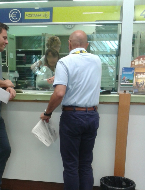 My hubby on the left trying to hold back his laughter as he talks with the post office manager
